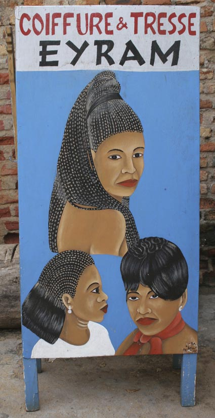 One side of a very large sandwich sign advertising the Coiffure & Tresse EYRAM beauty salon sign, one XL woman's head, 2 Lg women's heads, side 2