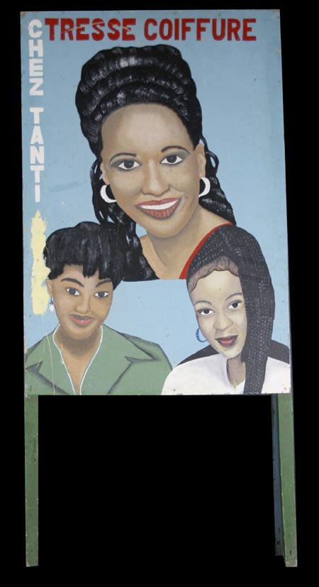 3 women's heads hand-painted on one side of a sandwich sign advertising the Chez Tanti salon, side B