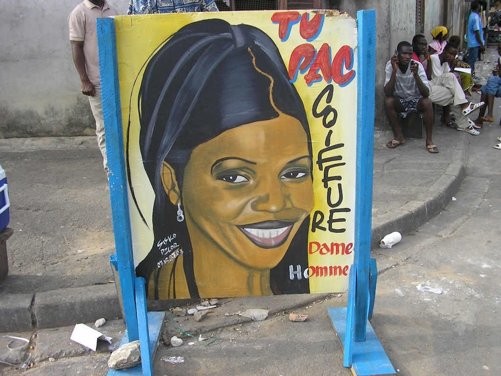Largest 2-sided sign commercial art sign advertising the Tu Pac Coiffure Salon with one large head on each side, woman side, on the stand in use on the street